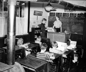 In this 1940 photo, Agnes Lynch teaches six students at the Wildwood school. The school, located in the northeast corner of Spokane County was wired for electric lights by the REA.  Wildwood was the last log schoolhouse in the county.