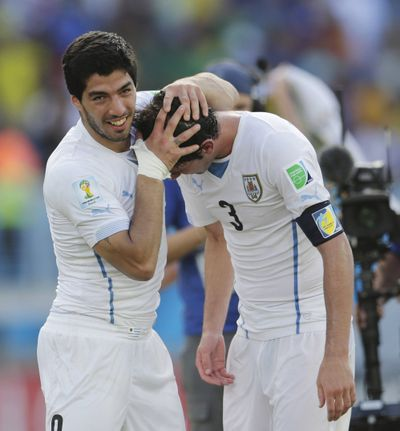 Uruguay's Luis Suarez, left, celebrates with Diego Godin following their 1-0 win over Italy on Tuesday. (Associated Press)