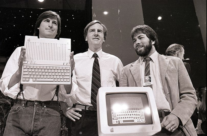 In this April 24, 1984, photo, from left, Steve Jobs, John Sculley and Steve Wozniak, unveil the new Apple IIc computer in San Francisco. (Associated Press)