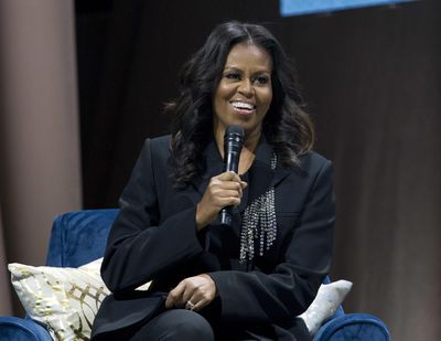 """In this Nov. 17, 2018,  photo, former first lady Michelle Obama speaks to the crowd as she presents her anticipated memoir """"Becoming"""" during her book tour stop in Washington. Obama's first project since """"Becoming"""" is more about her readers than about herself. """"Becoming: A Guided Journal for Discovering Your Voice"""" will be published Nov. 19, 2019, by Clarkson Potter, an imprint of Penguin Random House. (Jose Luis Magana / Associated Press)"""