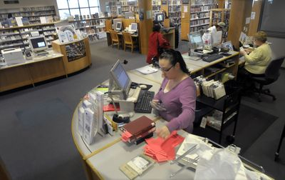 Christina York works behind the desk of the East Side branch of the Spokane Public Library on  Friday. The Spokane library system may be forced to cut 4 percent from its budget, and could compensate for the loss by closing a neighborhood branch.  (Christopher Anderson / The Spokesman-Review)