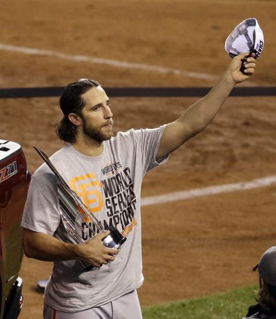 Giants pitcher Madison Bumgarner celebrates with the MVP trophy. (Associated Press)