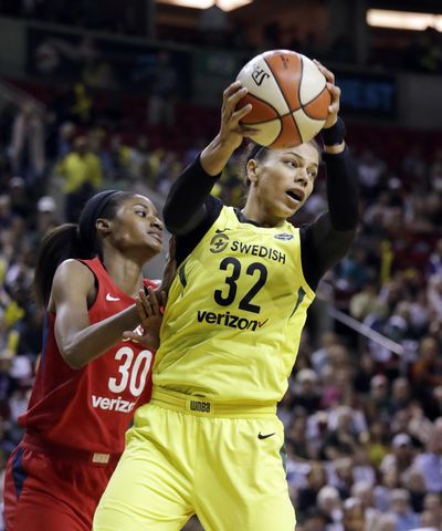 Seattle Storm's Alysha Clark (32) grabs a rebound in front of Washington Mystics' LaToya Sanders during the first half of Game 1 of the WNBA basketball finals Friday, Sept. 7, 2018, in Seattle. (Elaine Thompson / AP)
