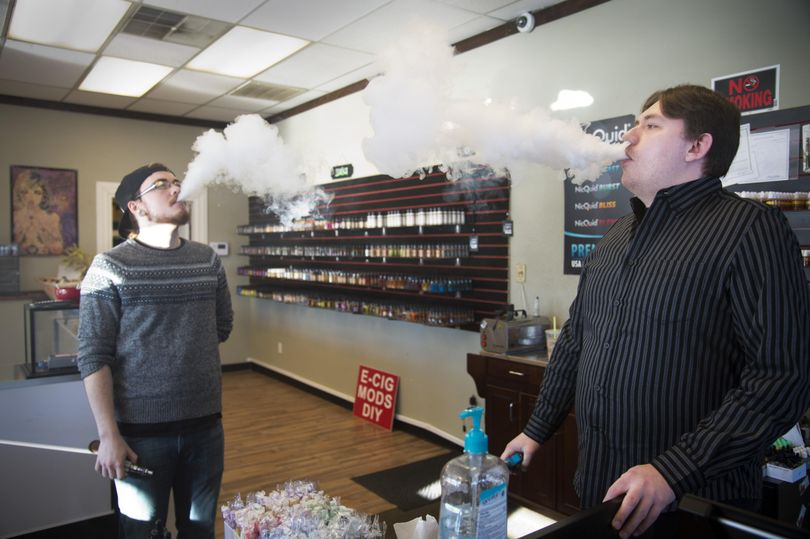 Gabriel Feller, left, and Luke Patterson release clouds of vapor at Smokin' Legal Vaperz vaping shop on Dec. 16, 2015. The two are salespeople at the shop, which sells vaping devices and juices that are inhaled using the battery-powered devices, sometimes called e-cigs. (Jesse Tinsley / The Spokesman-Review)