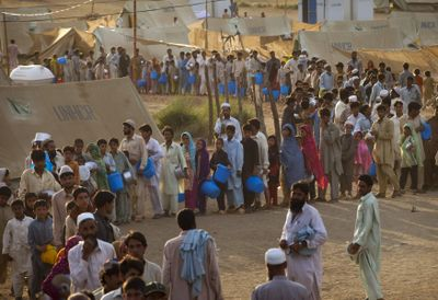 Displaced Pakistanis line up as they wait their turn during a food distribution at Chota Lahore Refugee Camp in Swabi, Pakistan, on Sunday.  (Associated Press / The Spokesman-Review)