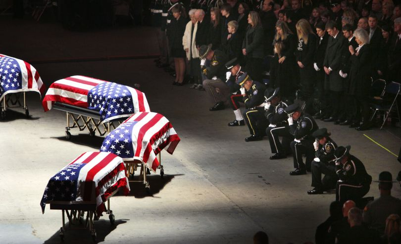 Police officers kneel at the caskets of four slain Lakewood officers during a memorial service Tuesday, Dec. 8, 2009, at the Tacoma Dome. The memorial was just a week after the officers were gunned down in a coffee shop before the start of their shift, Nov. 29. Killed were Sgt. Mark Renninger, 39, and officers Ronald Owens, 37, Tina Griswold, 40, and Greg Richards, 42. (Elaine Thompson / Associated Press)