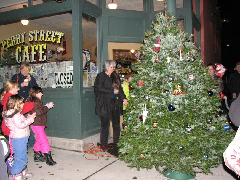 Pastor Debra Conklin plugs in the Christmas tree outside the Perry Street Cafe on Tuesday Dec. 14, 2010 (Pia Hallenberg)