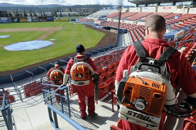 Inmate workers use leaf blowers to clean the stands at Avista Stadium on Monday. Some inmates from  Geiger Corrections Center perform labor in and around Spokane while serving sentences.  (Jesse Tinsley / The Spokesman-Review)