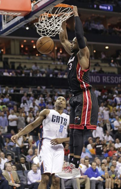 Miami Heat's Dwyane Wade (3) dunks against Charlotte Bobcats' Gerald Henderson (9) during a series-clinching 109-98 win. (Associated Press)