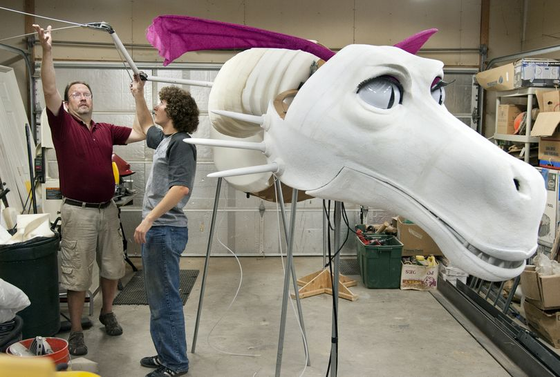 "Rustin Hall and his son Joseph unfold the wing structure of the 24-foot, 75-pound dragon they built for the University High School drama department production of ""Shrek."" (Dan Pelle)"