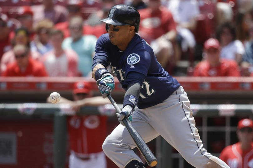 Leonys Martin of the Mariners bunts for a hit in the fifth inning. (John Minchillo / Associated Press)