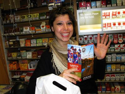 Barfen Parlak displays Spokane brochures, printed in German, at a shop called the Kiosk in Cologne, Germany.  (Doug Clark / The Spokesman-Review)