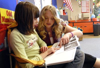 Lauren Puhek, of Central Valley High School, helps second-grader Josie Scribner with a reading exercise  Wednesday in a quiet corner at Greenacres Elementary School. Puhek, a WAVE scholarship recipient, will be the first in her family to attend college.    (J. BART RAYNIAK / The Spokesman-Review)