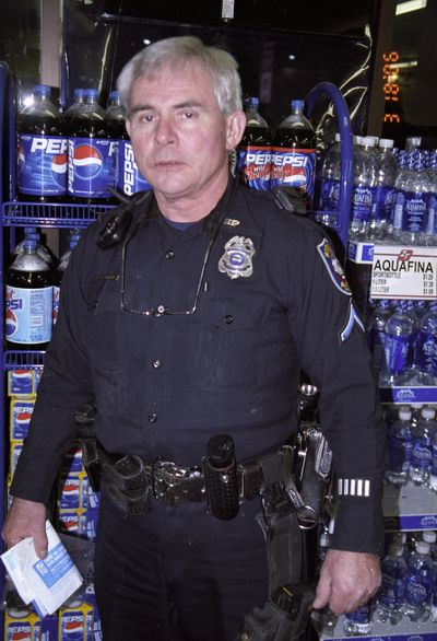 Spokane police Officer Karl F. Thompson Jr. is photographed following the March 18, 2006, confrontation with Otto Zehm. Thompson, according to court testimony, is holding Zehm's paycheck that Zehm at some point had in his hand. This was one of many photos provided to the jury.