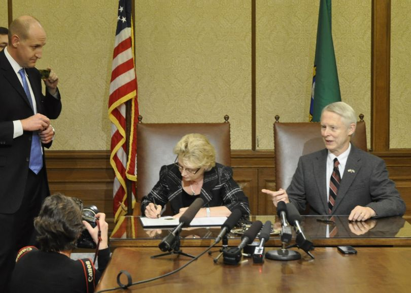 OLYMPIA -- Gov. Chris Gregoire signs the election results certifying Referendum 74, the same-sex marriage law, as Secretary of State Sam Reed looks on and communications director Cory Curtis, at left, holds a handful of pens from the signing. (Jim Camden)