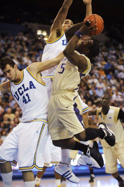 Washington's Justin Dentmon (5) goes to the basket as UCLA's Nikola Dragovic (41) and Drew Gordon defend.   (Associated Press / The Spokesman-Review)