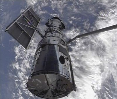 In this image from NASA TV, the Hubble Space Telescope is shown being held by the robotic arm from Shuttle Atlantis on Wednesday, setting the stage for five days of formidable repairs. (Associated Press / The Spokesman-Review)