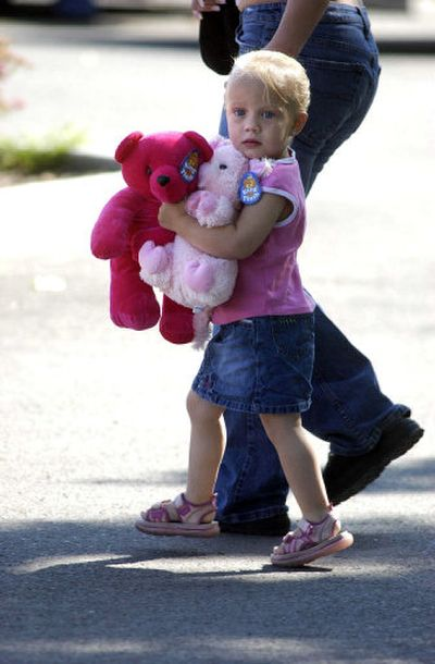 An unidentified girl carries teddy bears into Kootenai Medical Center in Coeur d'Alene. Dozens of children and families dropped off gifts, cards and balloons for Shasta Groene.   (Jesse Tinsley / The Spokesman-Review)