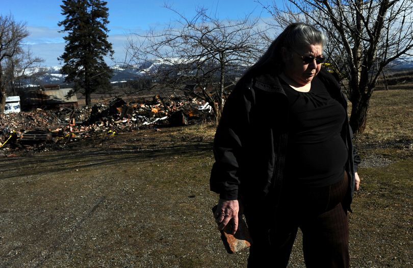 """""""I've lost my childhood home,"""" said Plummer, Idaho, resident Mariane Nomee, as she retrieved a brick from the burned rubble of the former Mary Immaculate School in DeSmet on Thursday. Nomee lived most of her childhood at the boarding school. (Kathy Plonka)"""
