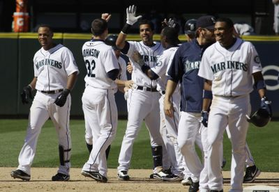 Franklin Gutierrez, center, is feted after his game-winning hit. (Associated Press / The Spokesman-Review)