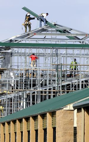Work crews attach sheets of roofing to a corner building section of the new addition at Self Storage on North Foothills Drive in Spokane.  (Dan Pelle / The Spokesman-Review)