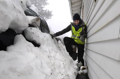 Avista meter reader Rachel Rushing struggles her way to a gas meter buried in snow between a pickup truck and a house on the 3800 block of south Hatch Road in Spokane on Thursday. She was unable to view the dials on the meter.  (Dan Pelle / The Spokesman-Review)