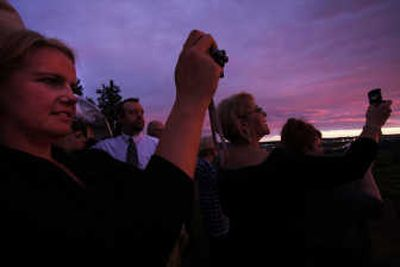Ginger Carter, left, and other attendees watch and take photos of the sunset just outside the dining tent during The Pour, held June 7 at the Arbor Crest Cliff House.   (Photos by Young Kwak / The Spokesman-Review)