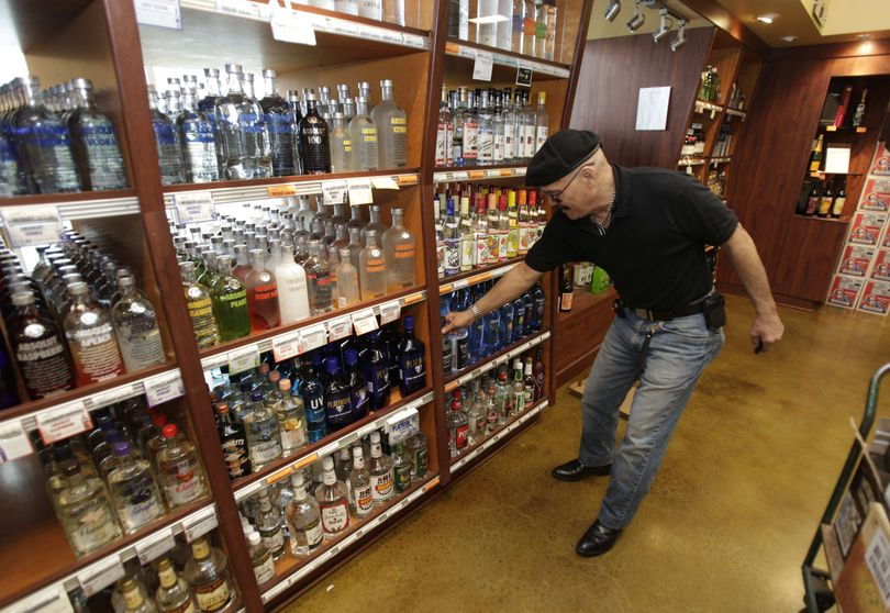 John TaJalle, of Federal Way, Wash., compares bottles of lower-priced gin as he shops in a Washington state liquor store in Seattle.  (Associated Press)