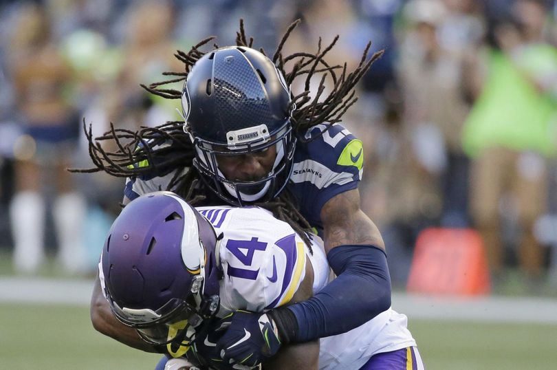 Seahawks cornerback Richard Sherman tackles Vikings wide receiver Stefon Diggs. (Elaine Thompson / Associated Press)