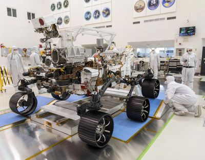 In this Dec. 17, 2019 photo made available by NASA, engineers watch the first driving test for the Mars 2020 rover Perseverance. (J. Krohn)
