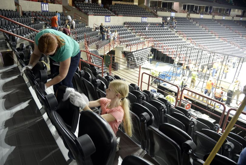 Volunteer Ellie Labrucherie, 8, and her mother Amanda, left, wipe down seats in the Spokane Arena Thursday, June 30, 2016. Volunteers from local Jehovah's Witness congregations will scrub and scrape around every seat and walkway of the Spokane Arena before their three-day convention. Church officials say that the church likes to leave their meeting spaces in better condition than when they arrived. More than 50 JW congregations will assemble for a three-day meeting July 1-3 at the Arena, a group estimated to be 6200 people. The evangelical group also invites everyone who would like to know more about their beliefs to attend also. There will be two sessions, morning and afternoon, each day. (Jesse Tinsley/SR photo)