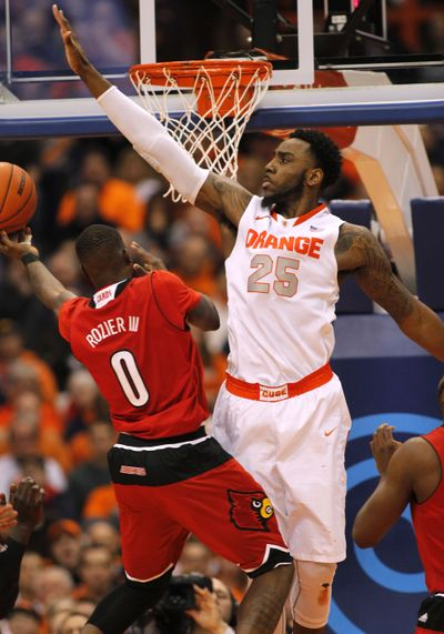 Syracuse's Rakeem Christmas, right, blocks a shot by Louisville's Terry Rozier. Syracuse upset the 12th-ranked Cardinals 69-59. (Associated Press)