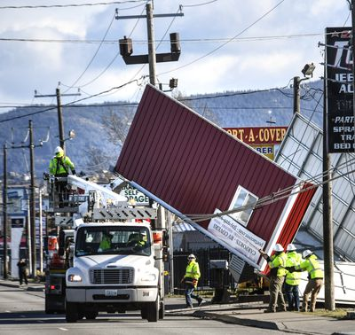 Crews work to free a carport blown into power and cable lines on the 16660 block of East Sprague in Spokane Valley, Wash., after high winds hit the area, Wednesday, Jan. 13, 2021,  (DAN PELLE/THE SPOKESMAN-REVIEW)