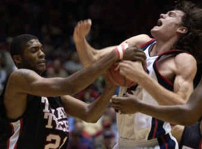 Texas Tech's Devonne Giles, left, ties up Gonzaga's Adam Morrison in the first half of Saturday's game in Tucson, Ariz. Morrison led the Bulldogs with 25 points.  (Dan Pelle / The Spokesman-Review)