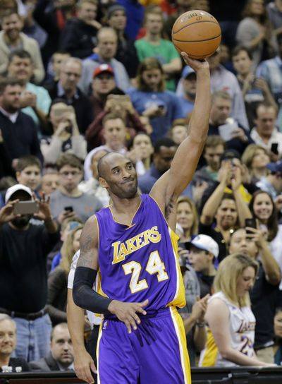 Kobe Bryant acknowledges crowd after hitting milestone. (Associated Press)