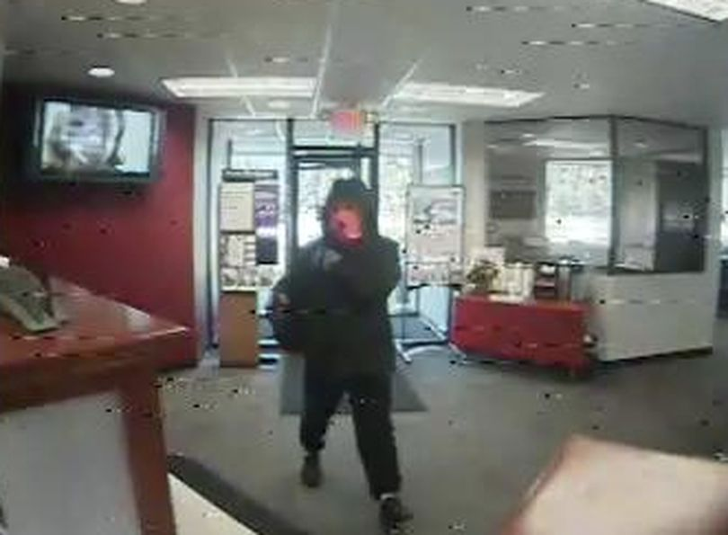 A gunman in a large parka and an orange ski mask robbed a bank in Rathdrum Thursday. Surveillance photos show the man entering the Wells Fargo,16234 North Highway 41 , at 11:37 a.m. (Rathdrum Police Department)