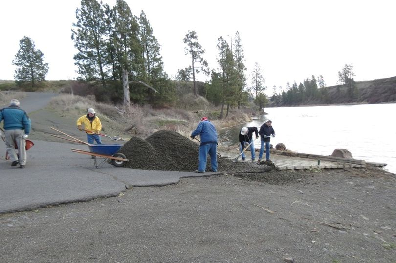 Gravel is spread by muscle power at the Amber Lake boat access by members of the Inland Empire and Spokane fly fishing clubs on Feb. 25, 2016. (Jim Ahearn)