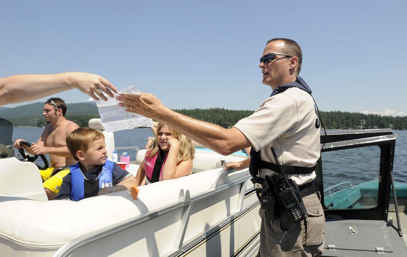 Spokane Sheriff's Deputy Jay Bailey accepts a boat registration form while he talks to boaters about the new boater education law. (Jesse Tinsley)
