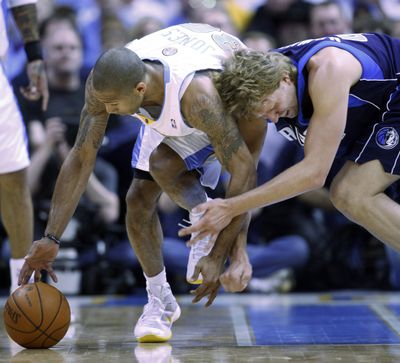 Denver's Dahntay Jones, left, picks up a loose ball against Dallas' Dirk Nowitzki during the Nuggets' series-clinching win at Denver.  (Associated Press / The Spokesman-Review)