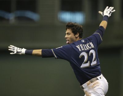 Milwaukee's Christian Yelich gives the 'safe' call as he crosses first base, beating the throw to drive in the game-winning run in the Brewers' 4-3 win over the Chicago Cubs on Monday in Milwaukee. (Aaron Gash / AP)