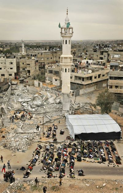 Palestinians take part in  Muslim Friday prayers on the street outside a destroyed mosque, where only the minaret still stands, in Beit Lahiya, Gaza Strip, on Friday.  (Associated Press / The Spokesman-Review)