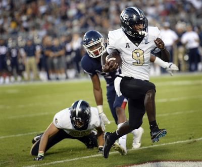 Central Florida running back Adrian Killins Jr. (9) runs the ball in for a touchdown during the first half of an NCAA college football game against Connecticut on Thursday, Aug. 30, 2018, in East Hartford, Conn. (Stephen Dunn / Associated Press)