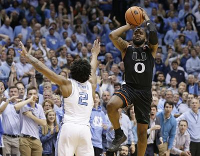 Miami's Ja'Quan Newton (0) shoots the game-winning shot as time expires while North Carolina's Joel Berry II (2) defends during the second half of an NCAA college basketball game in Chapel Hill, N.C., Tuesday, Feb. 27, 2018. Miami won 91-88. (Gerry Broome / Associated Press)