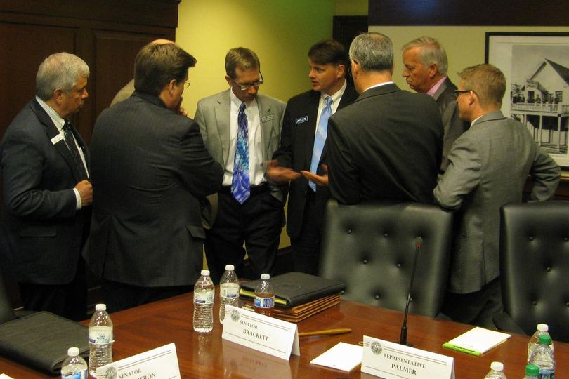 Conference committee members huddle with Deputy Attorney General Brian Kane and Legislative Services Director Eric Milstead before reconvening Friday afternoon (Betsy Russell)