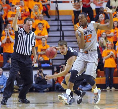 Oklahoma State guard Market Brown, right, tries to move out of the way of Gonzaga Guard Kevin Pangos, center, while the referee calls a foul during the first half of Gonzaga's 69-68 win over the Cowboys in Stillwater, Okla. (Brody Schmidt / Fr79308 Ap)