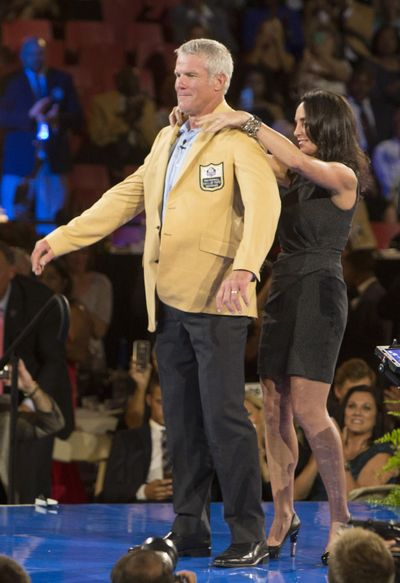Brett Favre receives his gold jacket from his wife, Deanna, at the Pro Football Hall of Fame  dinner on Thursday. (BOB ROSSITER / Associated Press)