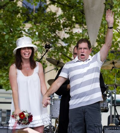 After saying their wedding vows, Jack Gibson and Kimberly Knox  turn to greet the crowd of family, friends and onlookers gathered at the main stage at Pig Out in the Park on Saturday in Riverfront Park. (Colin Mulvany / The Spokesman-Review)