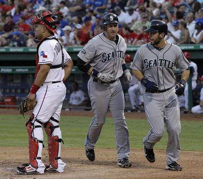 Mariners' Mike Carp, center, and Dustin Ackley head (Associated Press)