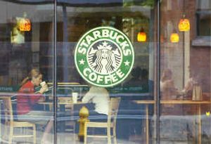 Customers sit inside a Starbucks Coffee shop in downtown Seattle. Java junkies often must journey more than two blocks to find a Starbucks, which the company sees as a problem, its chief executive said Thursday.   (Associated Press / The Spokesman-Review)