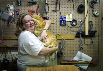heryle Hopkins holds Tiger the cat as she visits the veterinary clinic in the maintenance room of the Union Gospel Mission veterinary clinic Wednesday.   (Christopher Anderson / The Spokesman-Review)